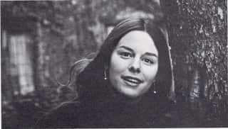 Portrait of Jane Mickelson as a young woman. She has long brown hair and is smiling and looking directly into the camera.